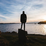 The Starting Point and Foundation of a Proper Worldview - Weekly Blog Post by Dr. Craig Biehl - man standing on rock by water's edge at sunset