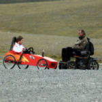Trials as a Price and Platform to Display Christ - Weekly Blog Post by Dr. Craig Biehl - Men in wheelchair & cart in open countryside