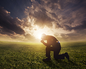 Gleanings from The Religious Affections (Part 21): Distinguishing Sign Six: True Humility Accompanies Gracious Affections - Weekly Blog Post by Dr. Craig Biehl - man kneeling in front of sunset